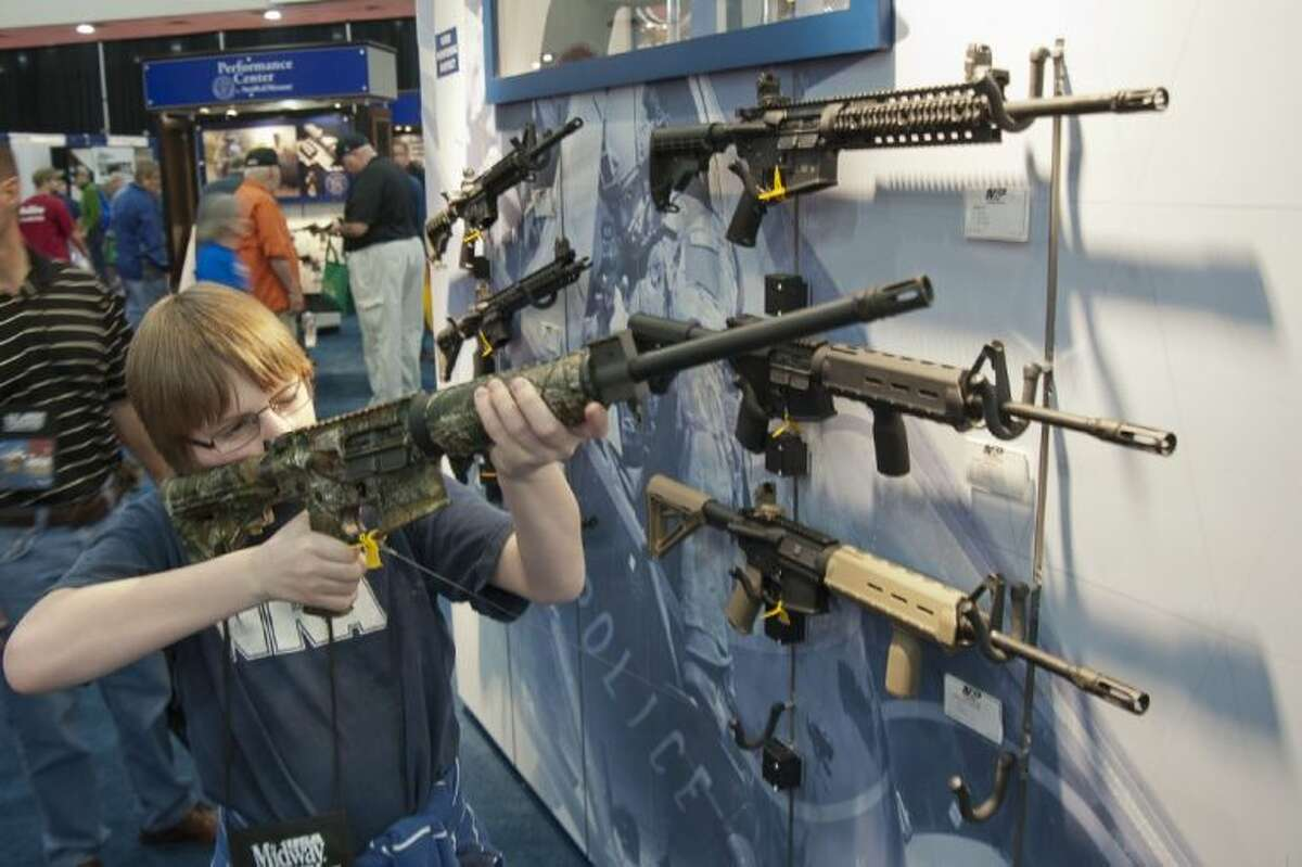 A young man who chose not to give his name sizes up an assault style rifle during the National Rifle Association's annual convention Friday in Houston.