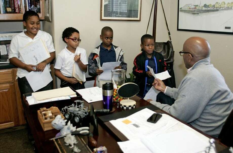 In this Oct. 16, 2013 photo, H.O.P.E. Farms Executive Director Gary Randle talks with Andre Willis, 10, Charles Jackson, 8, Jachin Floyd, 7, and Travion Powell, 7, about their grades at H.O.P.E. Farm in Fort Worth, Texas Ex. Fort Worth Narcotic officer Broadwater wrote Life in the Fishbowl about a 1 1/2 year undercover operation that netted 41 arrests in May of 2006. But for Broadwater, the narcotics officer in the middle of the investigation, another number stood out. As a result of the sting and the convictions, 104 children were left without one or more of their parents. Photo: Bob Booth