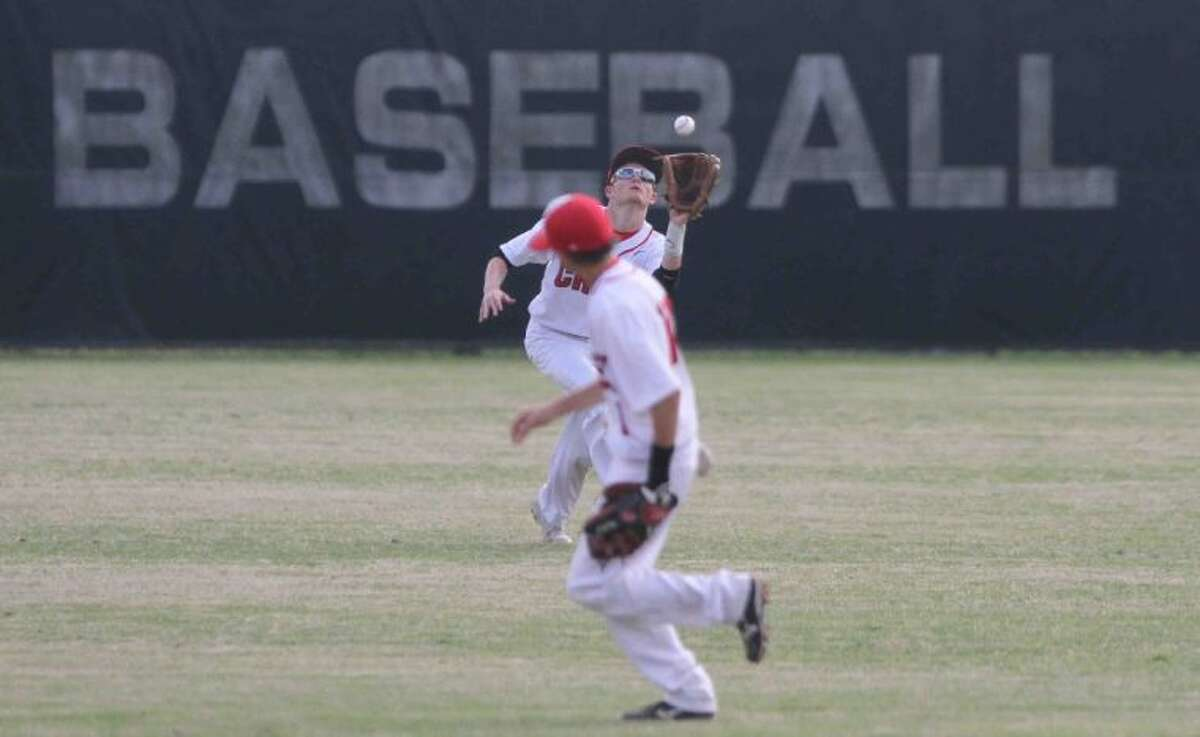 Caney Creek outfielder Kyle Jolly catches a fly ball as second baseman Kyle Goolsby follows the play during a District 18-4A game against Rudder on Saturday. To view or purchase this photo and others like it, visit HCNpics.com.