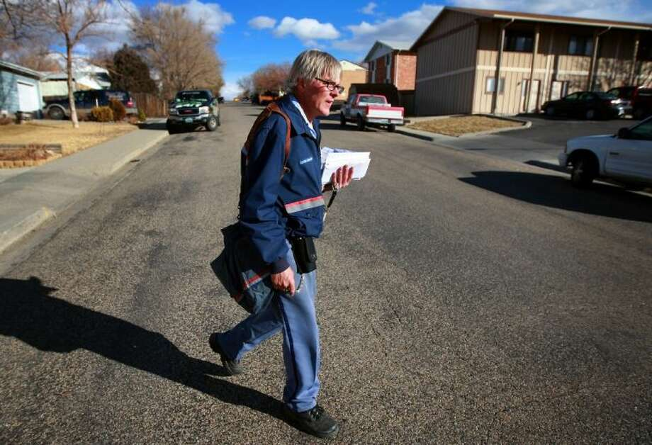 Mail carrier Lou Holscher walks his route Feb. 6 on East 7th Street in Casper, Wyo. Holscher has worked for the Casper Post Office for almost 30 years and said he has seen the volume of mail drop off significantly in recent years.