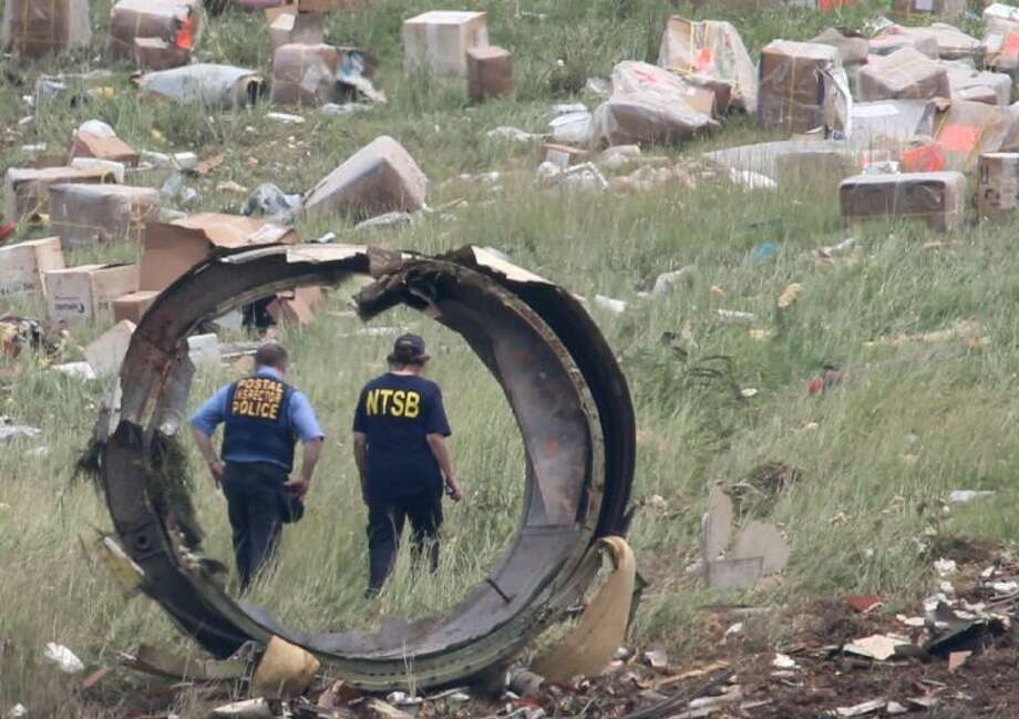 A postal Inspector officer and a NTSB investigator are seen through a section debris of a UPS A300 cargo plane after it crashed on approach at Birmingham-Shuttlesworth International Airport Wednesday.