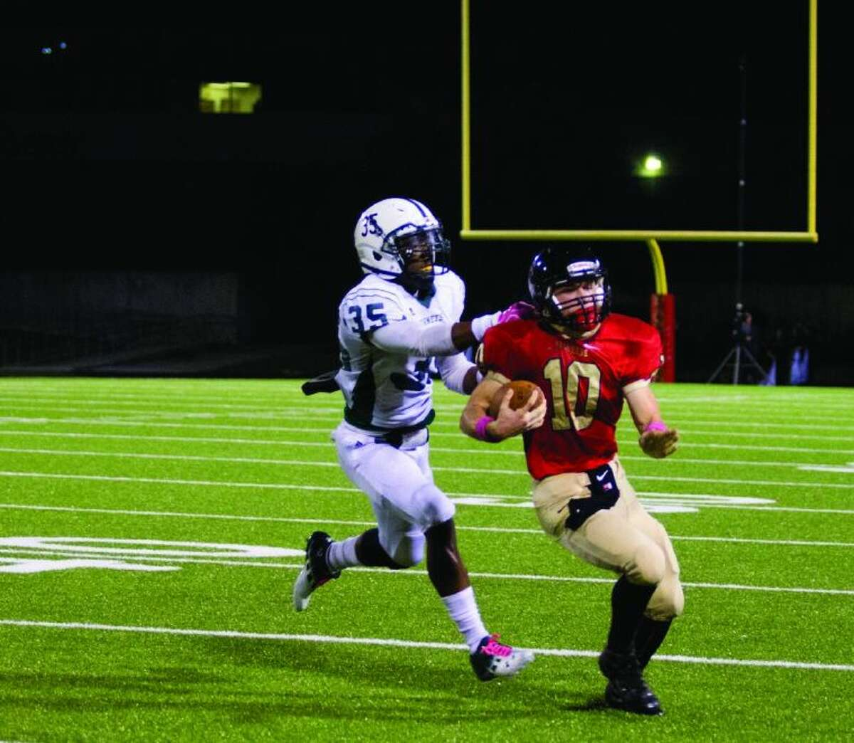 Caney Creek wide receiver Robert Gordon runs with the ball and is pushed out of bounds by Huntsville linebacker Keelan Greene during a game Friday night at the Moorhead Stadium in Conroe. Go to HCNPics.com to view and purchase this photo, and others like it.