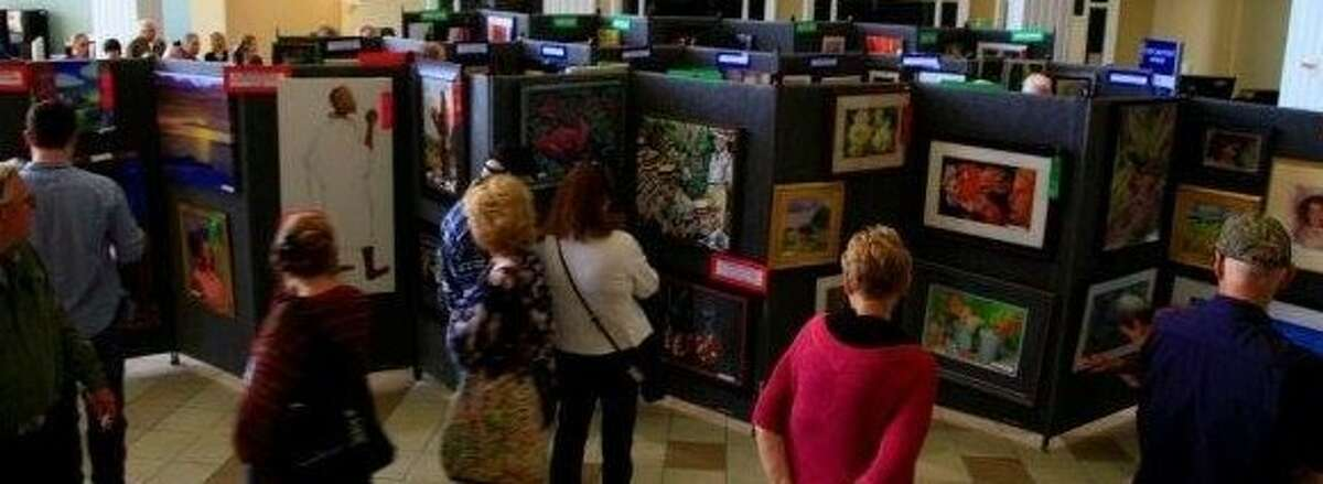 Guests look at some of the artwork which was entered in the Conroe Art League Spring Show.