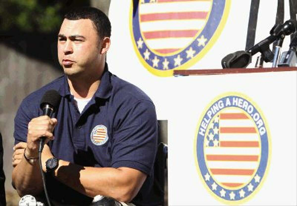 """U.S. Army Maj. Will Lyles addresses the crowd during a groundbreaking ceremony for his new home provided by """"Helping a Hero,"""" an organization that builds homes for wounded soldiers, in The Woodlands Wednesday. Go to HCNPics.com to view more photos from the event."""