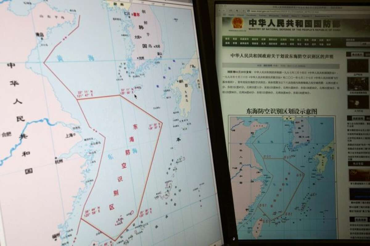 """Computer screens display a map showing the outline of China's new air defense zone in the East China on the website of the Chinese Ministry of Defense, in Beijing Tuesday. On Saturday Beijing issued a map of the zone - which includes a cluster of islands controlled by Japan but also claimed by China - and a set of rules that say all aircraft entering the area must notify Chinese authorities and are subject to emergency military measures if they do not identify themselves or obey Beijing's orders. Chinese characters in red in the center of the map at left reads: """"Air Defense Identification Zone in East China Sea."""""""