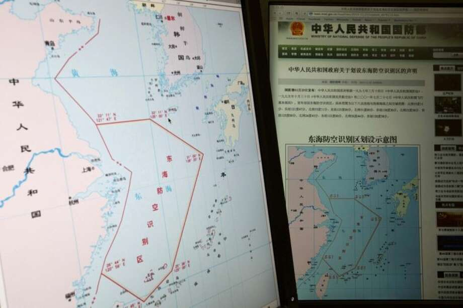 "Computer screens display a map showing the outline of China's new air defense zone in the East China on the website of the Chinese Ministry of Defense, in Beijing Tuesday. On Saturday Beijing issued a map of the zone — which includes a cluster of islands controlled by Japan but also claimed by China — and a set of rules that say all aircraft entering the area must notify Chinese authorities and are subject to emergency military measures if they do not identify themselves or obey Beijing's orders. Chinese characters in red in the center of the map at left reads: ""Air Defense Identification Zone in East China Sea."" Photo: Ng Han Guan"
