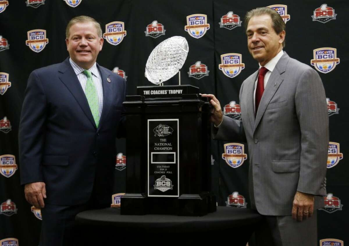 Notre Dame's Brian Kelly, left, and Alabama's Nick Saban pose with the BCS championship trophy in Miami.