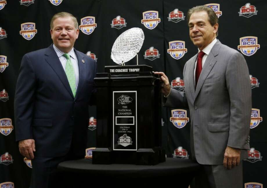 Notre Dame's Brian Kelly, left, and Alabama's Nick Saban pose with the BCS championship trophy in Miami. Photo: John Bazemore