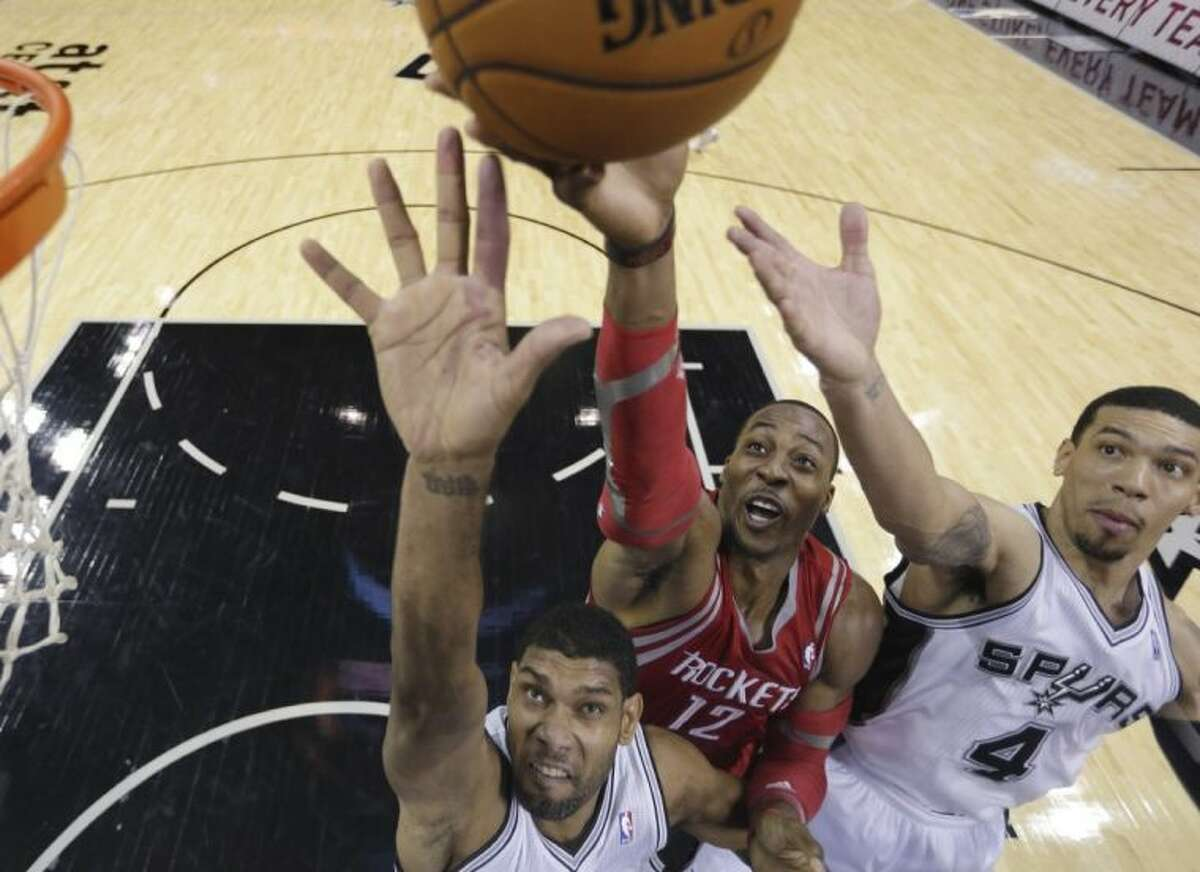Houston Rockets center Dwight Howard shoots over the San Antonio Spurs' Tim Duncan, left, and Danny Green during the first half of a preseason game Thursday in San Antonio.