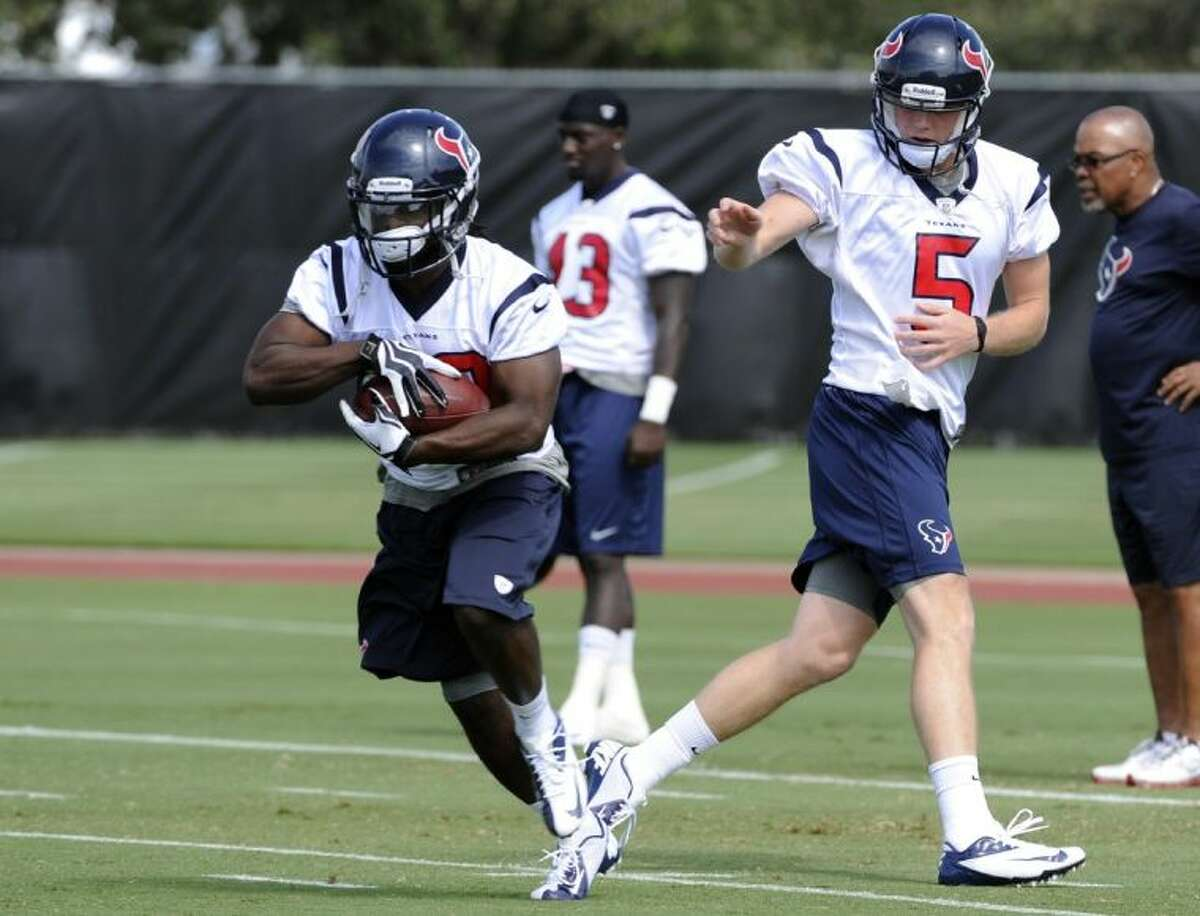 Deji Karim takes a handoff from Houston Texans rookie quarterback Collin Klein during workouts at the Texans' rookie minicamp Saturday in Houston.