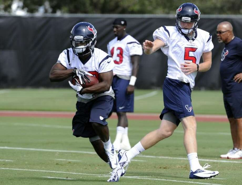 Deji Karim takes a handoff from Houston Texans rookie quarterback Collin Klein during workouts at the Texans' rookie minicamp Saturday in Houston. Photo: Pat Sullivan