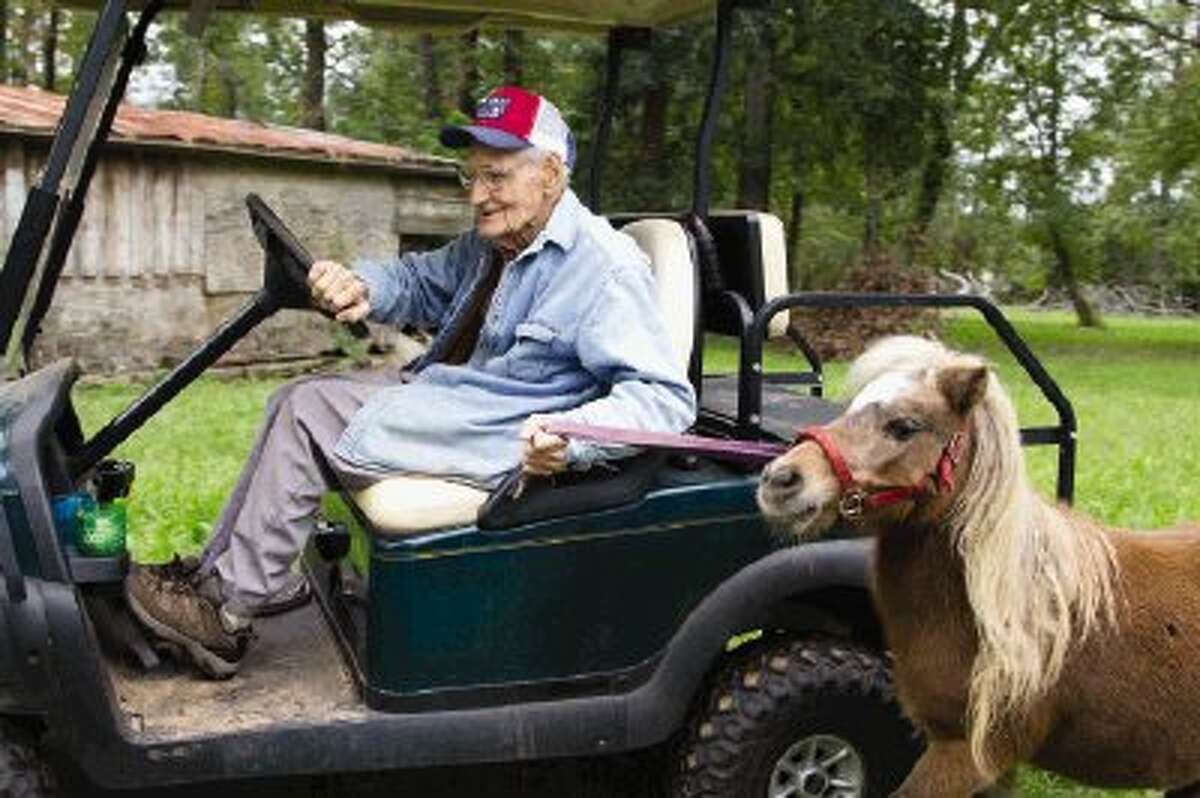 Ralph Riggs drives a golf cart while taking his miniature horse to a pasture on Tuesday afternoon in Willis. The Riggs celebrated their 80th anniversary on Monday and Ralph will cerebrate his 101st birthday on Tuesday.