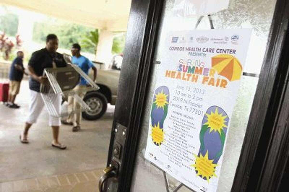 Vendors move items into the Conroe Healthcare Center prior to the center's Summer Health Fair Saturday.