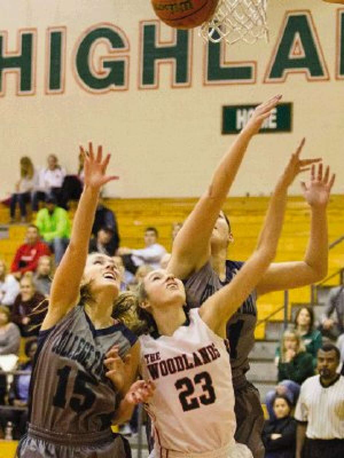 The Woodlands' Marxli Mettauer (23) shoots the ball as College Park's Cami Shafer (15) and Andrea Velez (41) attempt to gain control of the ball during a basketball game at The Woodlands High School. The Lady Highlanders won 58-20. Go to HCNPics.com to view and purchase this photo, and others like it.