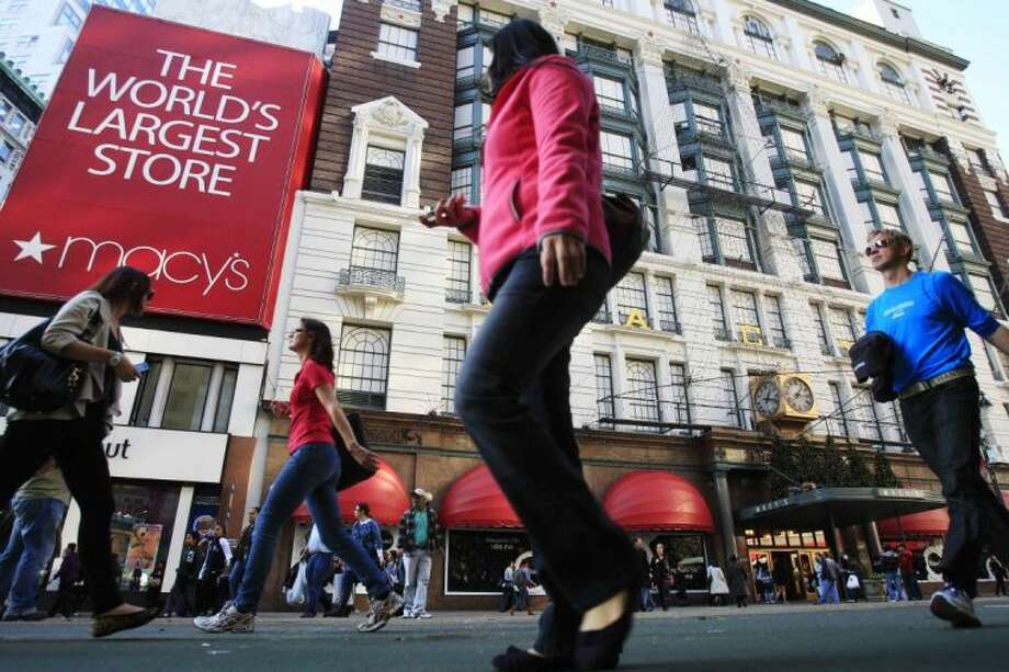 In this Nov. 8, 2011 file photo, pedestrians pass the Macy's department store in New York. Macy's Inc. reported its quarterly earnings on Wednesday,