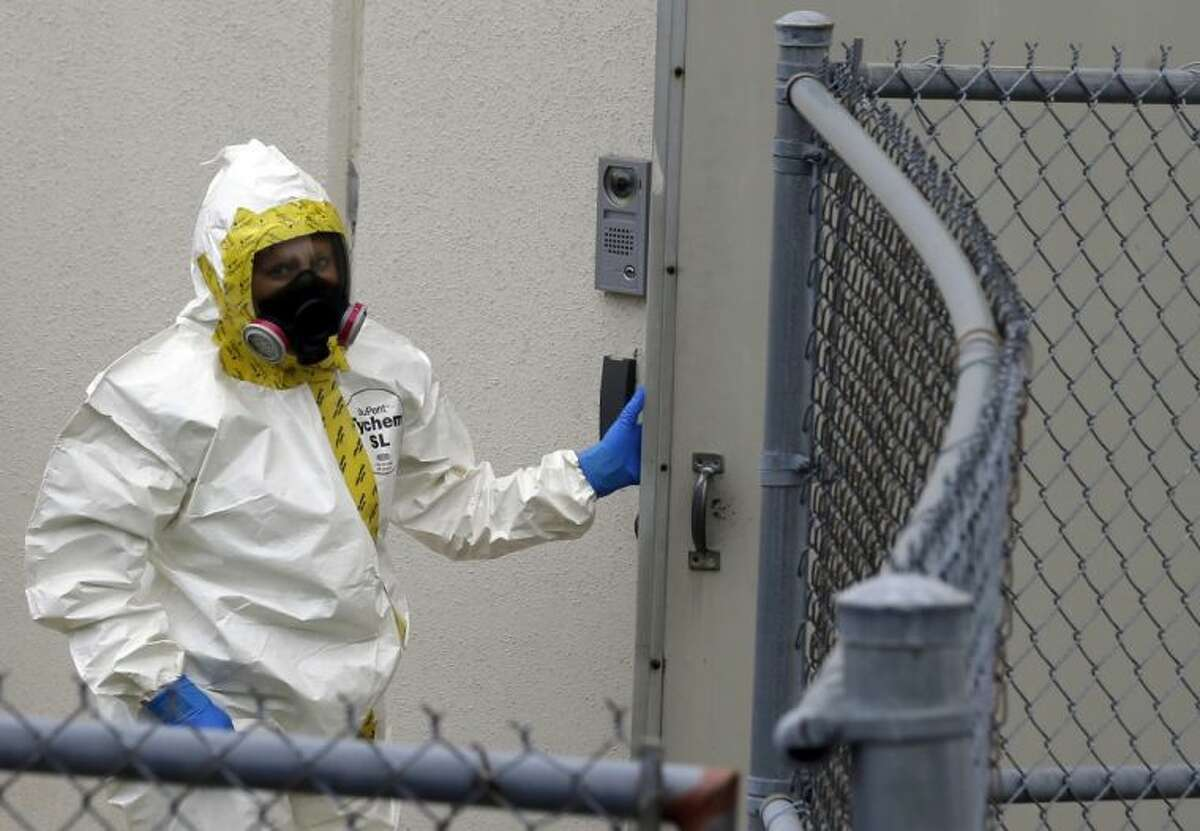 A Prince George's County, Md. firefighter dressed in a protective suit walks into a government mail screening facility in Hyattsville, Md., Wednesday.