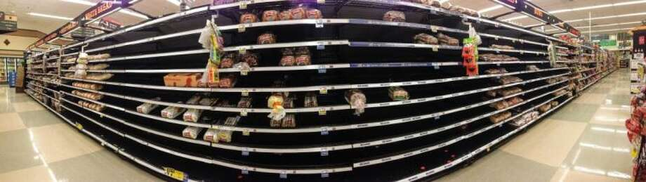 The bread shelves at an Arlington, Texas, Kroger are decimated and are in need of restocking after customers made a run on the store because of the ice storm, Sunday, Dec. 8, 2013. North Texas started to thaw out slightly Sunday after two days of a near standstill with icy roads and low temperatures. About 400 departures from Dallas-Fort Worth International Airport were canceled Sunday. It will likely be a couple of days before the ice that's coated the region melts completely. Photo: Tom Fox