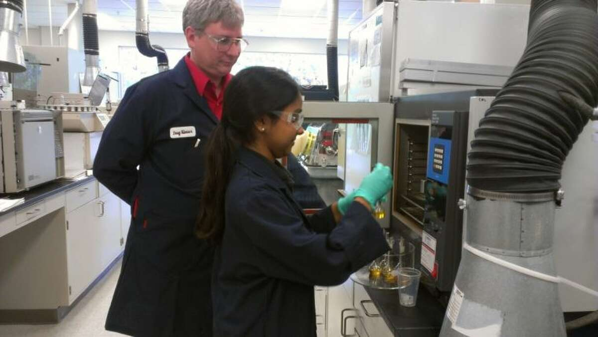 A high school summer intern learns how to operate testing equipment at Huntsman.
