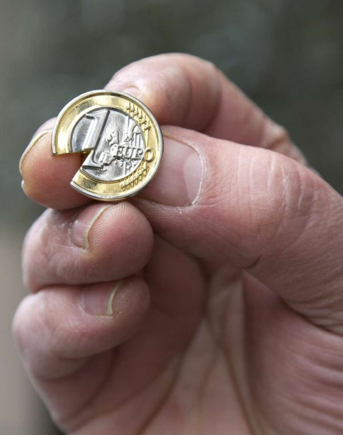 A Cypriot man, who did not wish to be identified, holds up a souvenir Cypriot euro coin lapel pin with a piece taken out near the Cypriot delegation building in Brussels on Sunday, March 24, 2013. The EU says a top official will chair a high-level meeting on Cyprus in a last-ditch effort to seal a deal before finance ministers decide whether the island nation gets a 10 billion euro bailout loan to save it from bankruptcy.