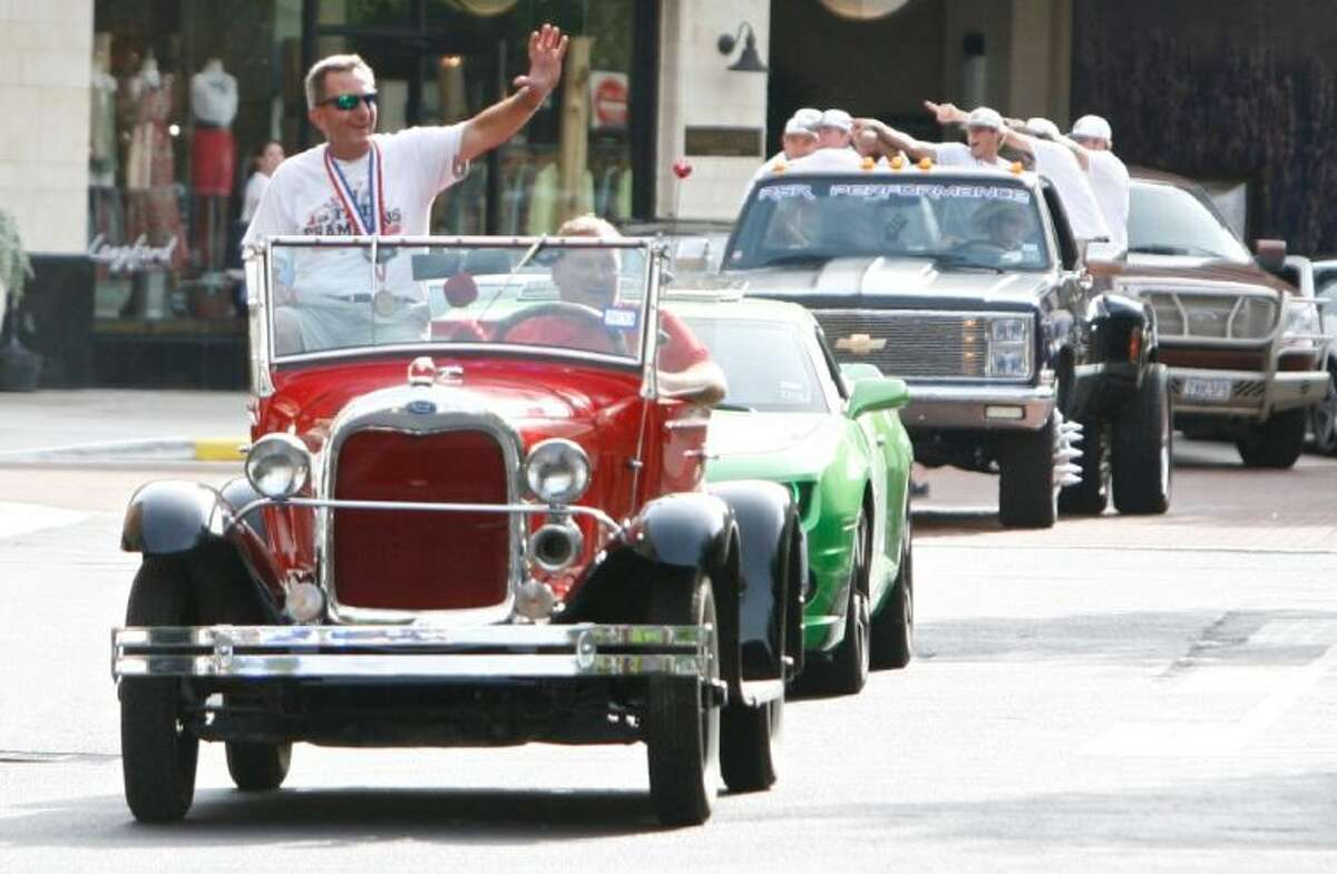 The Woodlands High School baseball coach Ron Eastman waves to residents from atop a classic car as the team entered Market Street in The Woodlands Tuesday. The parade honored the team's state championship win in Round Rock. To view or order this photo and others like it, visit: HCNPics.com.