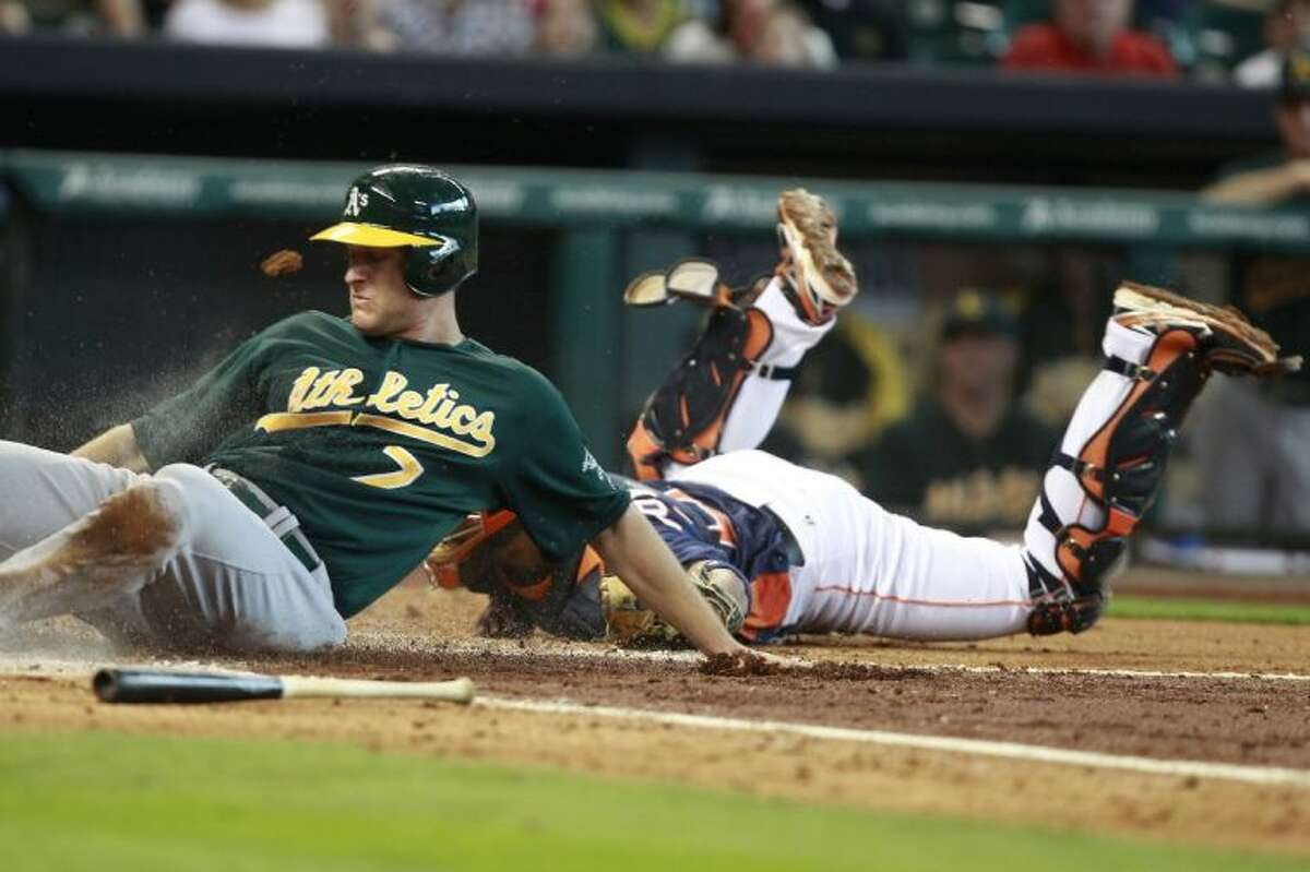 The Oakland Athletics' Nate Freiman, left, slides safely past Houston Astros catcher Carlos Corporan to score in the fourth inning. The Astros lost 6-2.