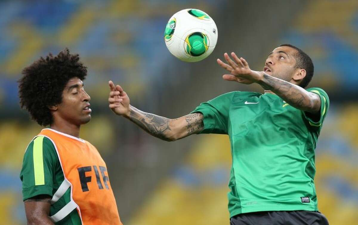 Brazil's Daniel Alves, right, and Dante practice during a training session at the Maracana stadium in Rio de Janeiro. Brazil faces Spain in the Confederation Cup finals today.