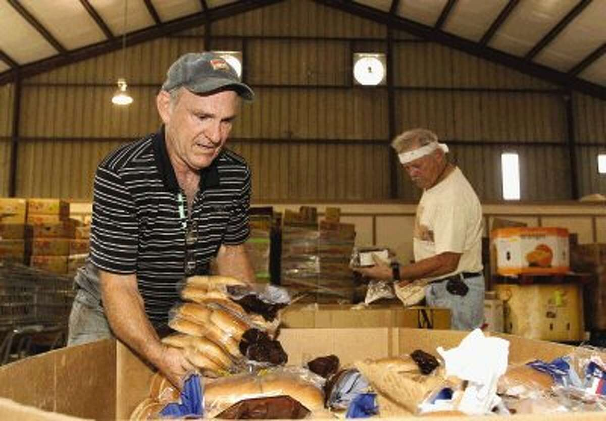 Volunteers Gerald Myers and Kevin Hare sort food into baskets at the MaTee's Food Pantry at First Baptist Church in Groceville Wednesday.
