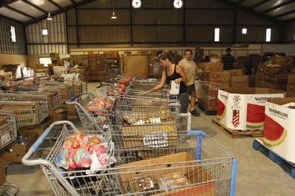 Volunteers, including Katherine Wineman, helps sort food and other items into baskets at the food pantry at First Baptist Church in Groceville Wednesday.