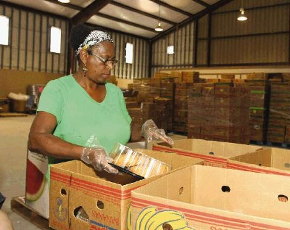 Bette Fisher sorts food items for baskets at the food pantry at First Baptist Church-Groceville Wednesday.