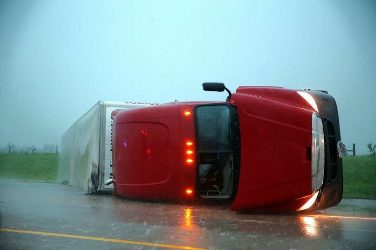 An overturned tractor-trailer rests on its side on the eastbound lanes of Interstate 40, just east of El Reno, Okla., after a reported tornado touched down Friday.