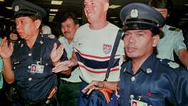 Former Barings bank trader Nick Leeson (center) is led through immigration by Singapore police officials at Changi airport shortly after he was freed from prison in Singapore in 1999.