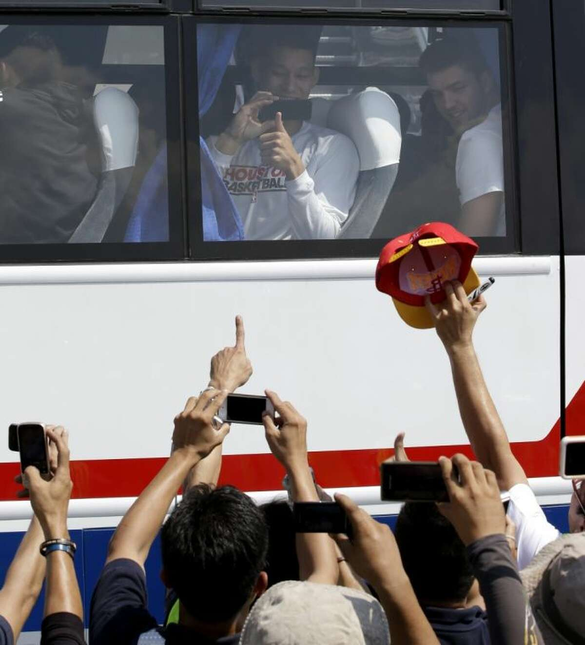 The Houston Rockets' Jeremy Lin takes photos of Filipino fans upon arrival Monday at the Ninoy Aquino International Airport near Manila, Philippines.