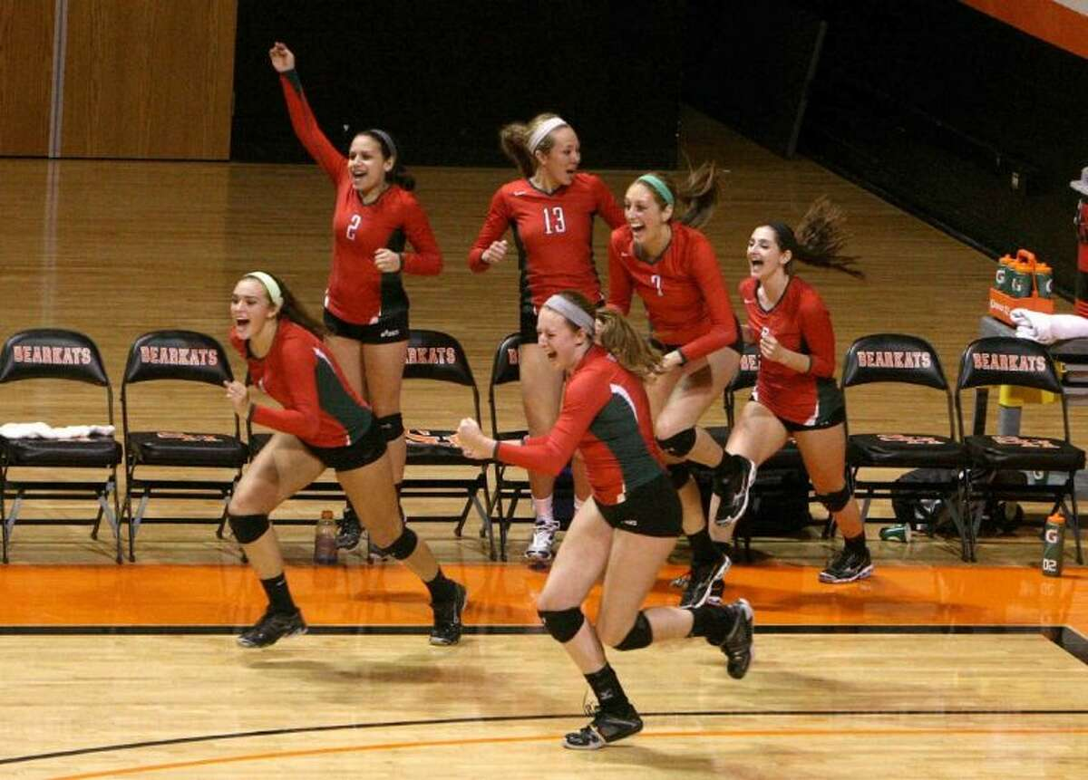 The Woodlands players celebrate after defeating Plano in straight sets to win the Region II-5A championship on Saturday at Bernard G. Johnson Coliseum on the campus of Sam Houston State University in Huntsville. To view or purchase this photo and others like it, visit HCNpics.com.