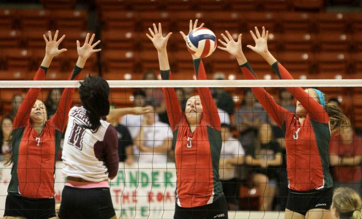 From left, The Woodlands' Maddie White, Morgan Eason and Madison McDaniel go up to block a shot by Plano's Gabby Howard during the Region II-5A championship match Saturday at Bernard G. Johnson Coliseum on the campus of Sam Houston State University in Huntsville. To view or purchase this photo and others like it, visit HCNpics.com.