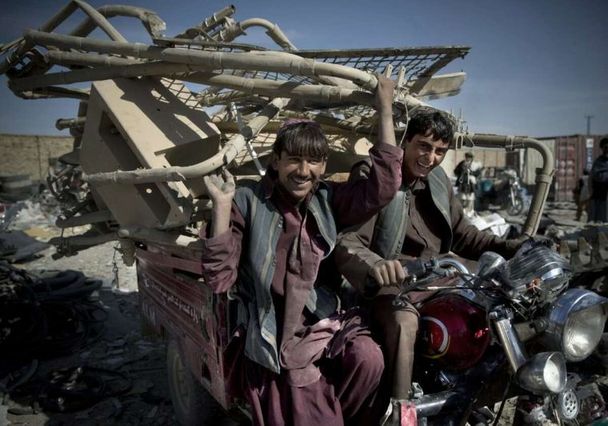This Saturday photo shows Afghan scrap collectors transport a load of destroyed U.S. equipment from the departing military in Kandahar, southern Afghanistan.