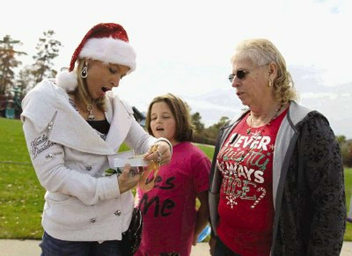 Samantha Bleike, left, reacts after opening a Christmas present in front of her daughter, Hannah, and their grandmother, Shirley Strait, during a visit to Northshore Park on Christmas Day Wednesday. The family opened presents and ate lunch at the park.
