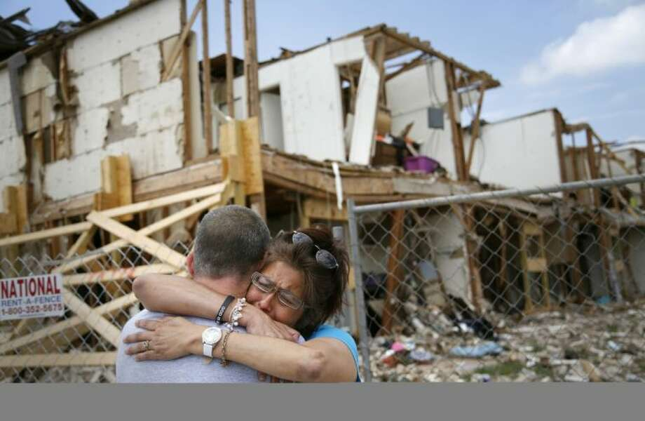 Shona Jupe, a resident of the apartment destroyed by the fertilizer plant explosion, hugs her friend as they met while she was visiting the site in West on Friday. Jupe was at the front door when the West Fertilizer Co. explosion happened. Photo: Kye R. Lee