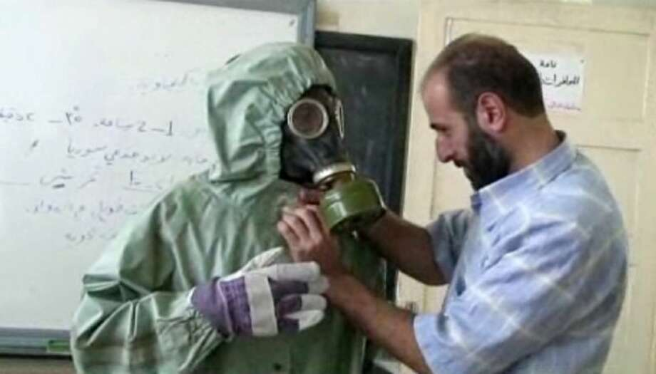 This image made from an AP video posted on Wednesday shows a volunteer adjusting a gas mask and protective suit on a student during a classroom session a on how to respond to a chemical weapons attack in Aleppo, Syria.