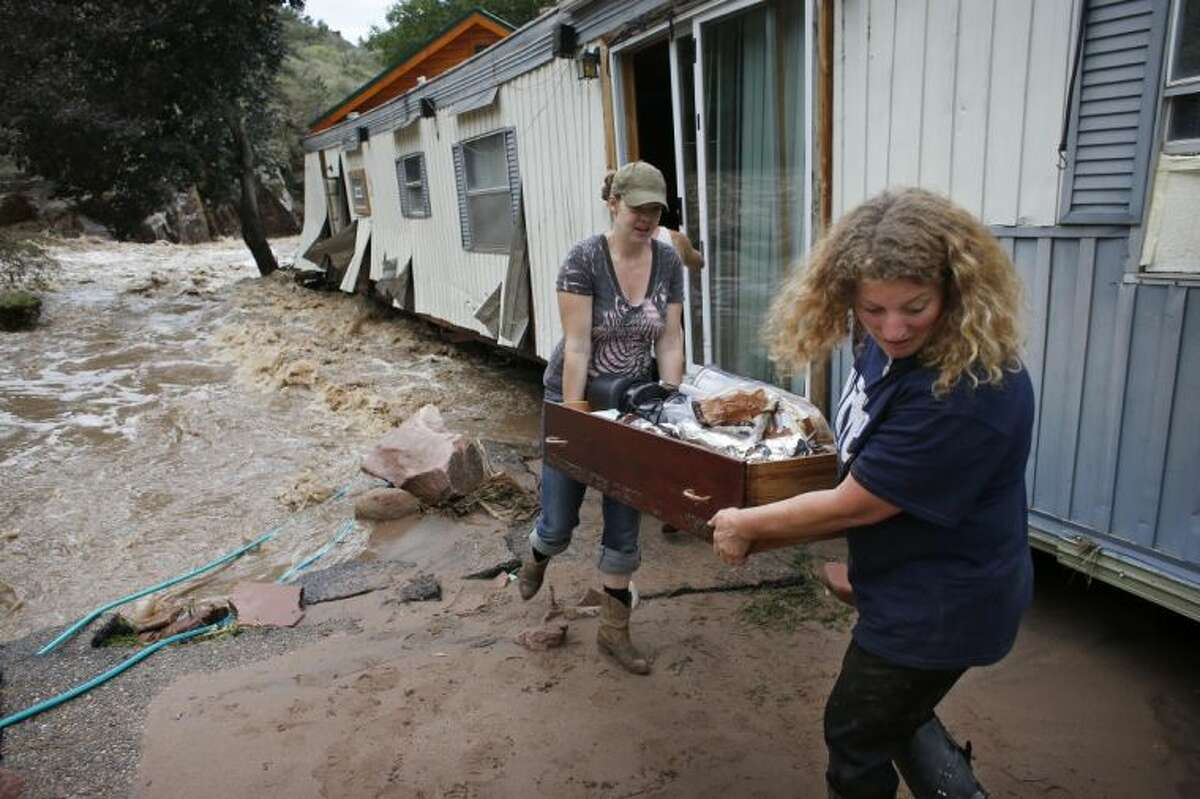 """In this Sept. 13, 2013 file photo, water rushes through her destroyed home as resident Holly Robb, left, and her neighbor Pam Bowers salvage belongings after storms that raged through the Rocky Mountain foothills in this photo made in Lyons, Colo. Two low-lying trailer parks in the small town, 20 minutes to the north of Boulder, bore the brunt of the recent flooding. """"I don't think we'll ever be able to go back,"""" said Robb."""