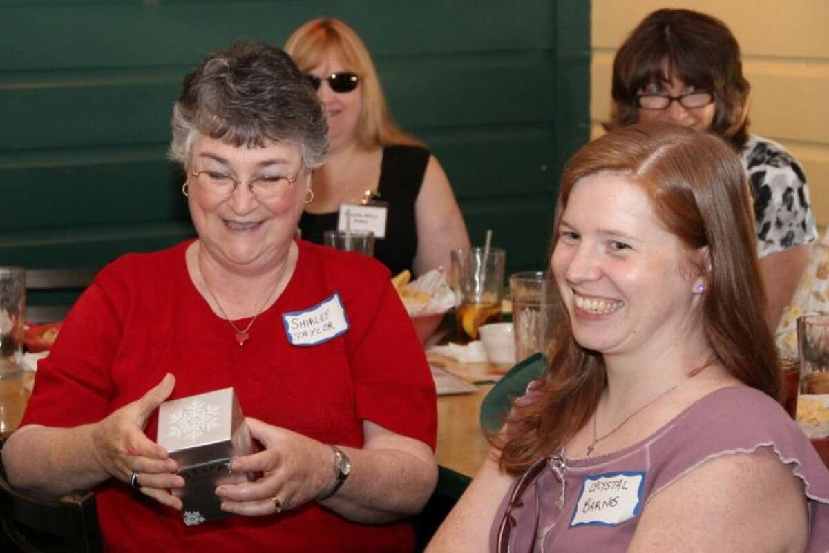 Author Shirley Taylor smiles as she receives the door prize during the July meeting of Writers on the Storm Saturday. She is seated next to Author Crystal Barnes.