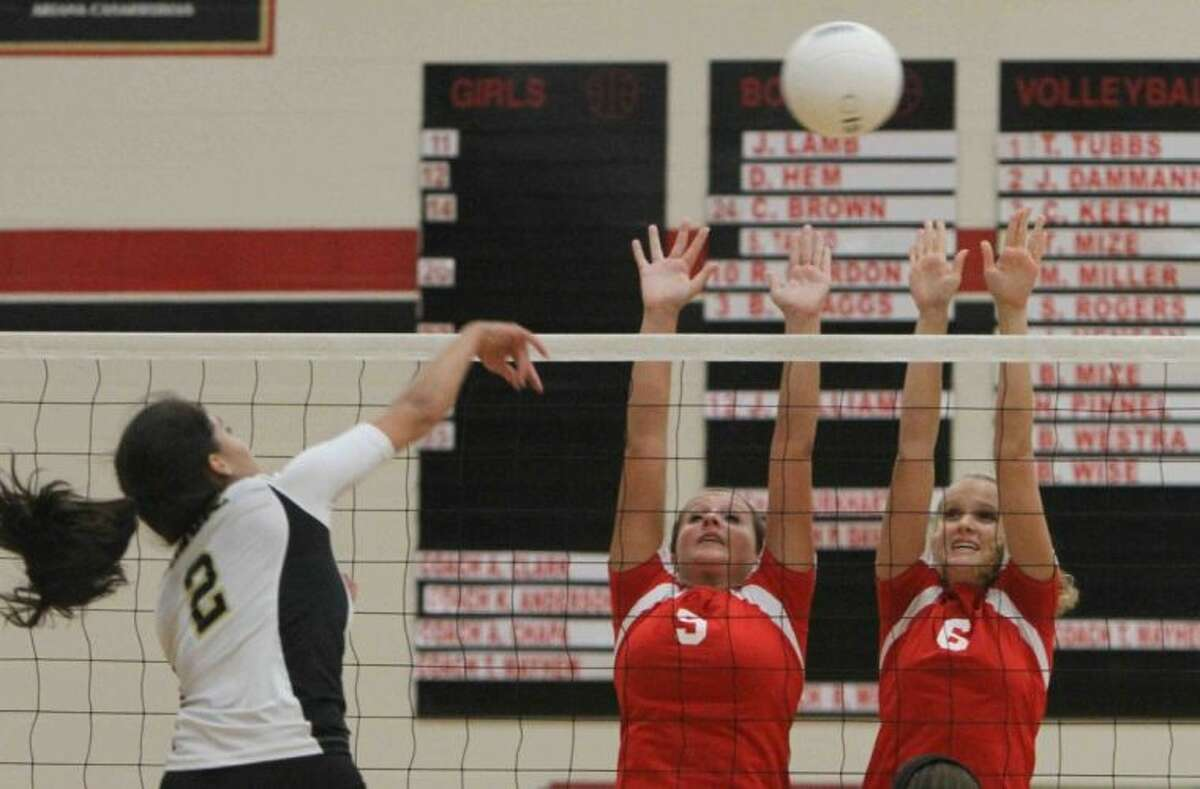 Caney Creek's Hayli Pinnell (9) and Olivia Wren (6) go up to block a shot by Conroe's Jules Vitela during a match on Tuesday at Caney Creek High School in Grangerland. To view or purchase this photo and others like it, visit HCNpics.com.
