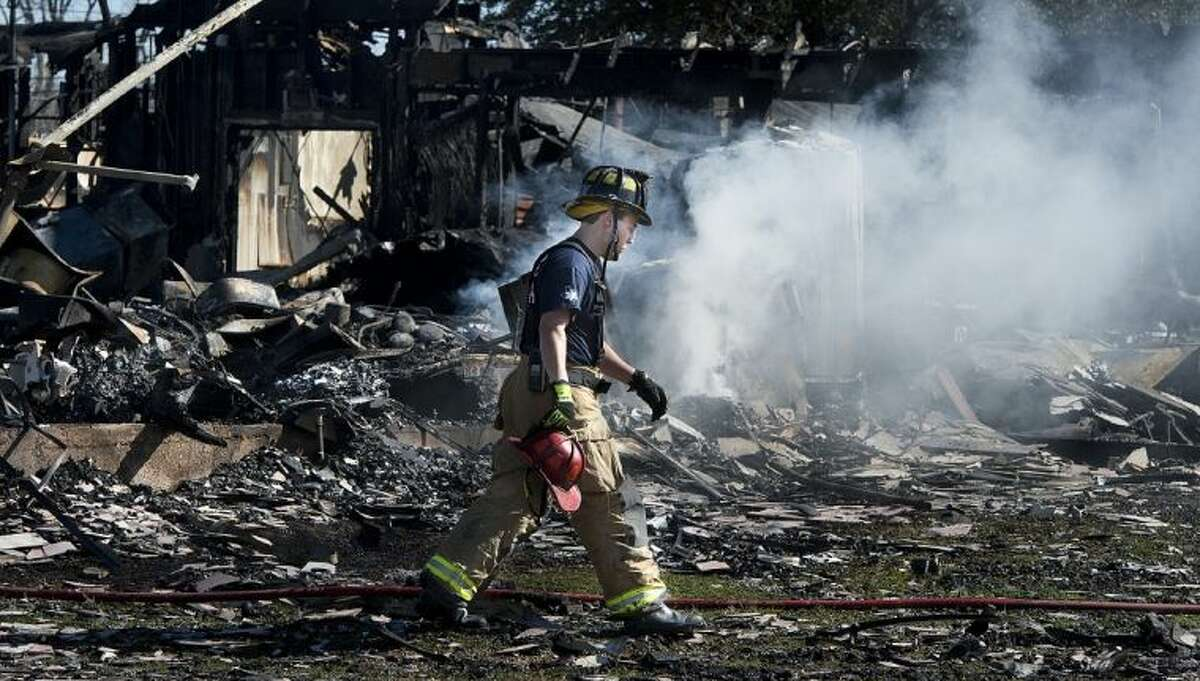 A Bryan firefighter walks across the smoking rubble of a Knights of Columbus Hall in Bryan Saturday.