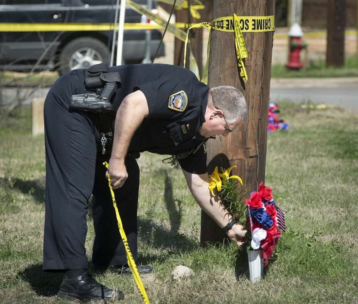 Bryan Police Officer Al Wescoat straightens flowers at a makeshift memorial near a Knights of Columbus Hall Saturday in Bryan.