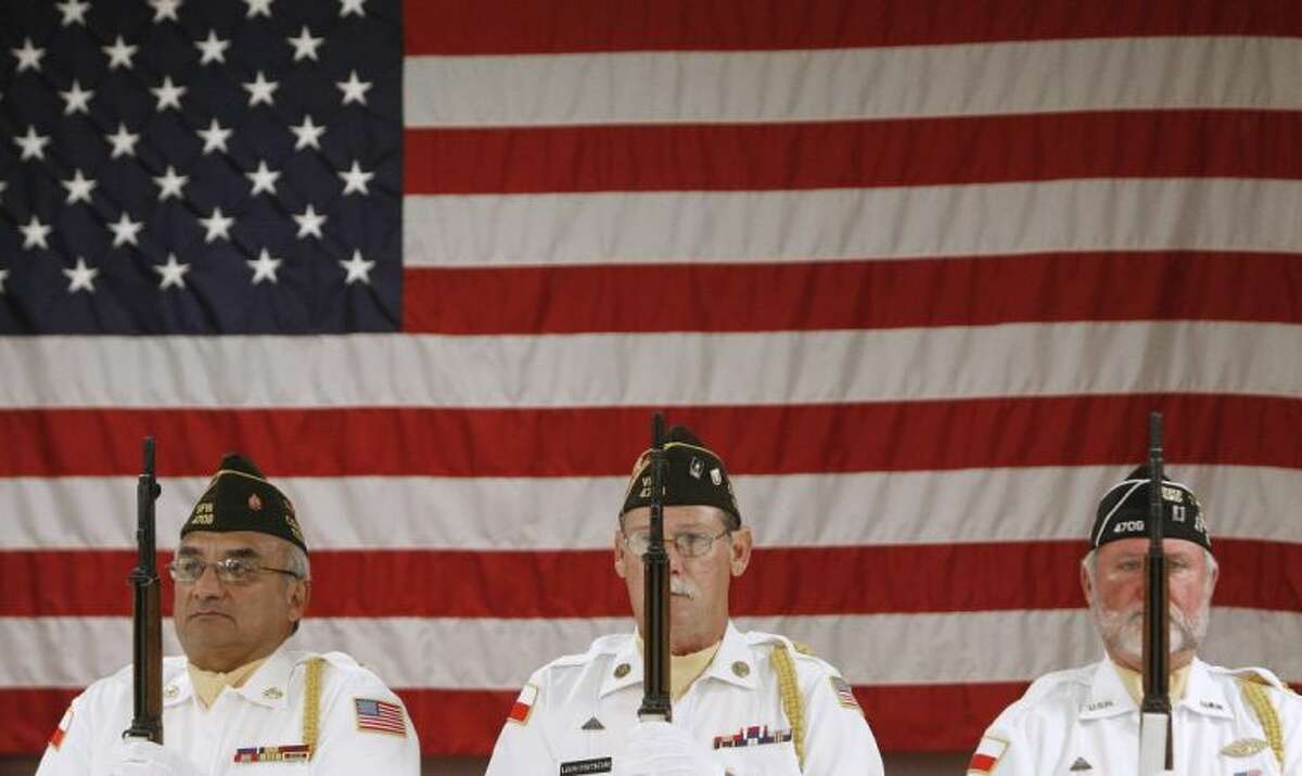Members of the Conroe VFW Post 4709 honor guard stand at attention in front of a large American flag during a Memorial Day ceremony Monday at the post in Conroe.