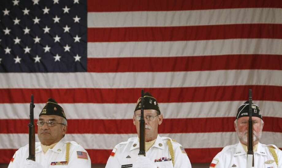 Members of the Conroe VFW Post 4709 honor guard stand at attention in front of a large American flag during a Memorial Day ceremony Monday at the post in Conroe. Photo: Staff Photo By Eric Swist