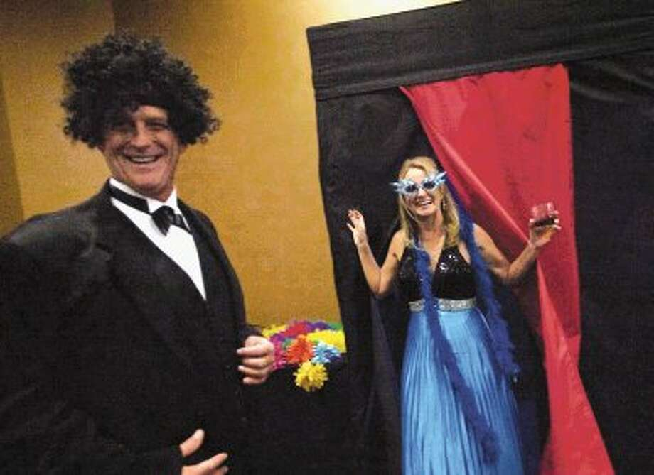 Laurie Long and Howard Perkins smile as they exit the Memorial Hermann photo booth during Saturday night's annual Greater Conroe/Lake Conroe Area Chamber of Commerce's Chairman's Ball at La Torretta Lake Resort & Spa on Lake Conroe.