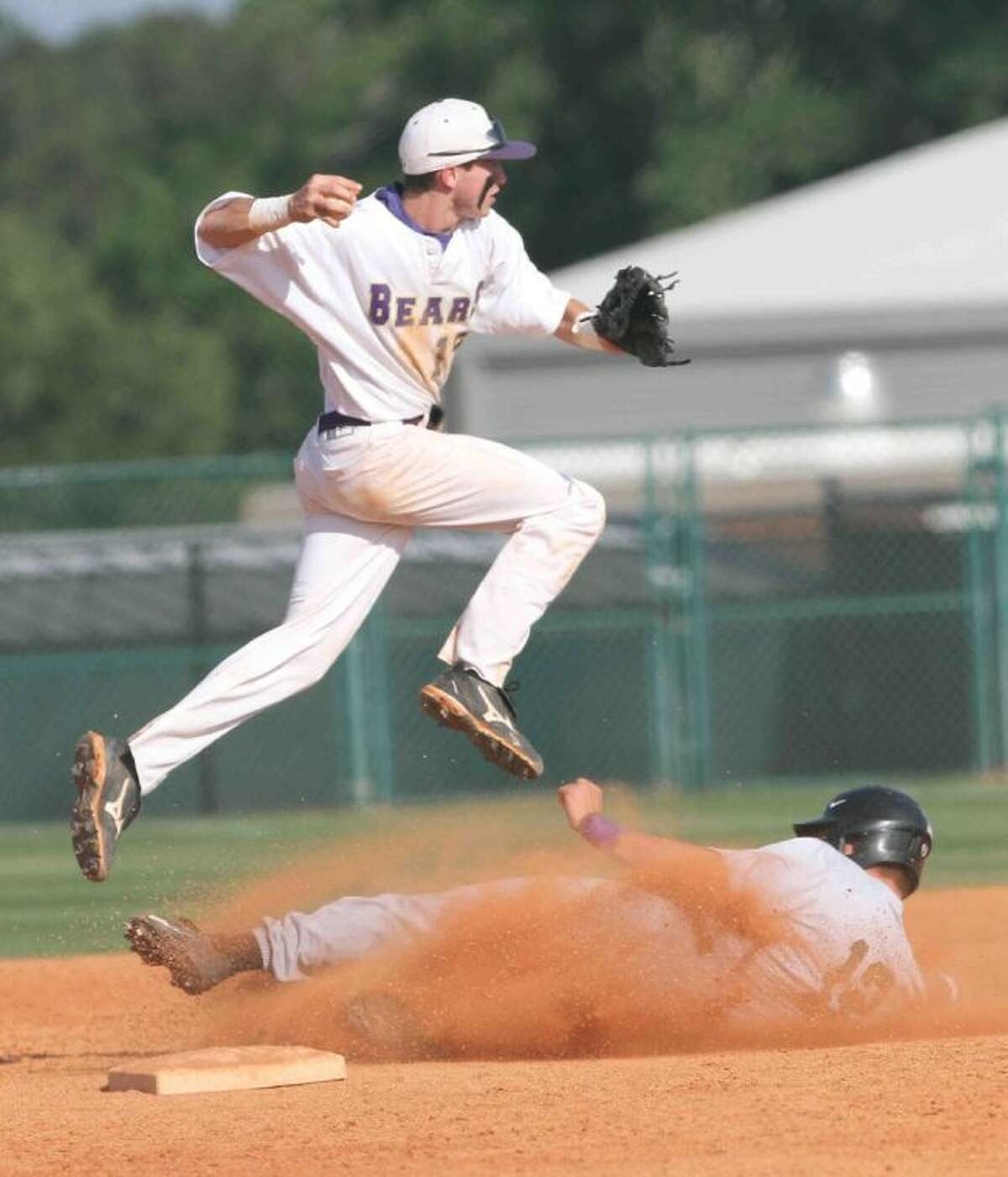 Montgomery shortstop Garrett Hrozek leaps up to turn a double play during a high school area baseball playoff game at Montgomery High School on Friday. Kingwood Park defeated Montgomery 2-1 in Game 1 before the Bears took Game 2 9-1. Go to HCNPics.com to view and purchase this photo, and others like it.