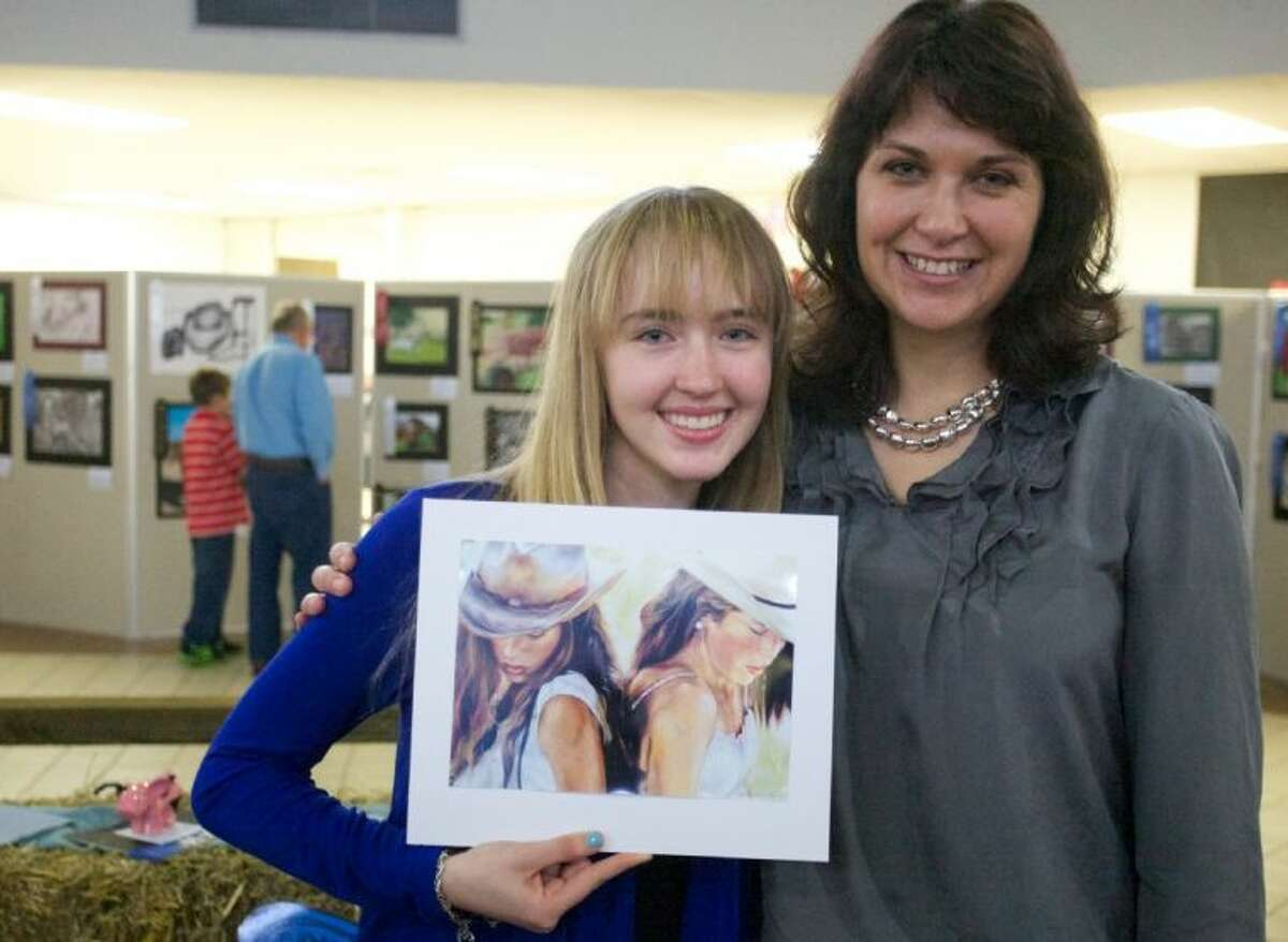 Best in Show winner Madison Chamberlain, of The Woodlands High School, displays her painting as she stands with her art teacher Jen Lucas for a photo during Saturday's Conroe ISD Western Art Show.