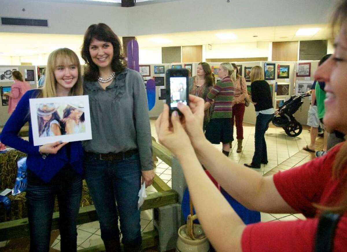 Annette Chamberlain, right, takes a photograph of her daughter Madison, a student at The Woodlands High School, with her art teach Jen Lucas during Saturday's Conroe ISD Western Art Show. Chamberlain won Best in Show with her painting.