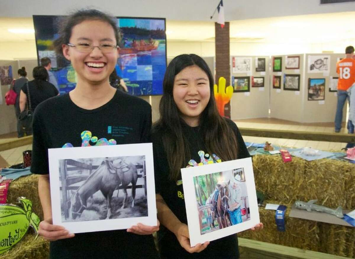 Claire Zhang, left, and Jenny Qu, students at McCullough Junior High School, display their award-winning paintings during Saturday's Conroe ISD Western Art Show.